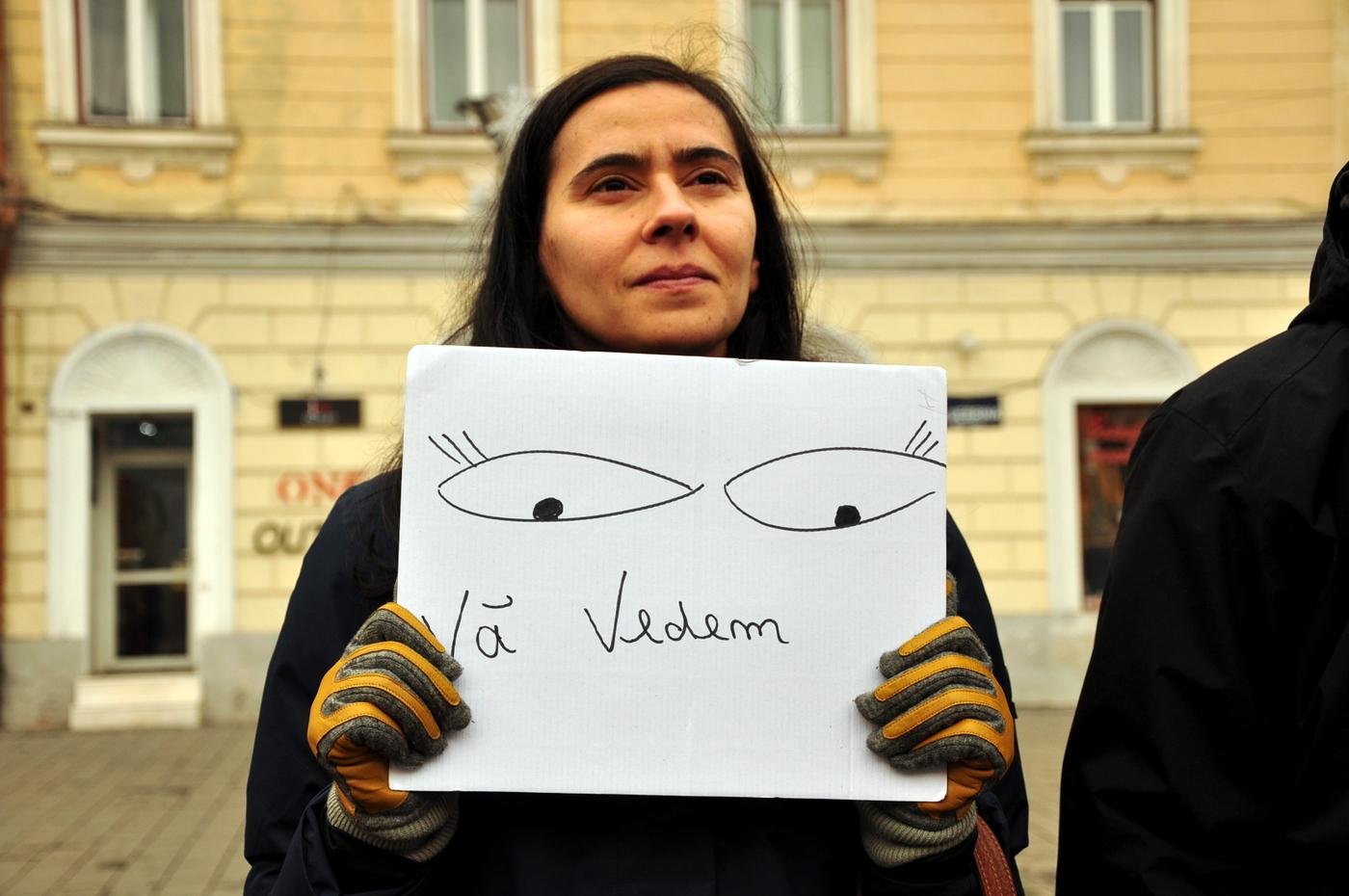Protestatar cu mesajul 'Vă Vedem', cu fața către sediul PSD Cluj